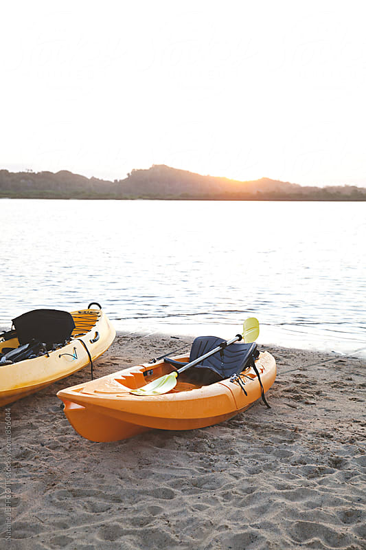 Yellow kayaks sit on a beach at sunset after a day paddling by Natalie JEFFCOTT for Stocksy United