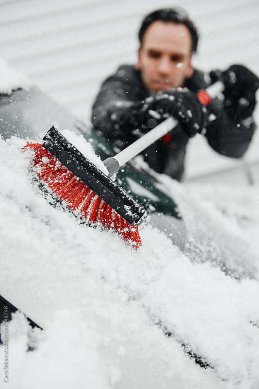 Man clears snow from his car following a winter storm by Cara Dolan for Stocksy United