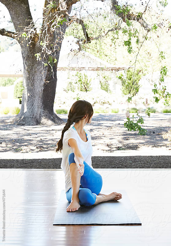 Woman doing yoga in yoga class at luxury resort by Trinette Reed for Stocksy United