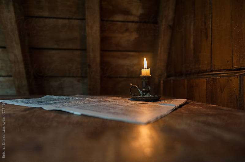 Candle light illuminates a newspaper on table by Rebecca Spencer for Stocksy United