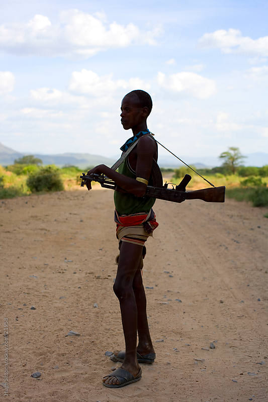Young Ethiopian man carrying AK47. Ethiopia by Hugh Sitton for Stocksy United
