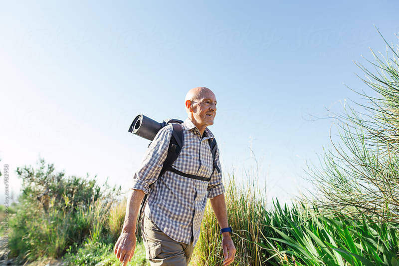 Senior man hiking on a mountain trail in a sunny day. by BONNINSTUDIO for Stocksy United