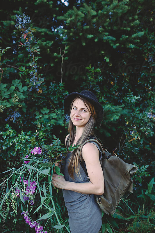 Portrait of a young woman with flowers and plants collected in the woods by michela ravasio for Stocksy United