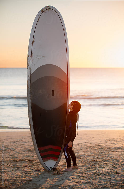 Small boy standing with large paddle board at sunset by Angela Lumsden for Stocksy United
