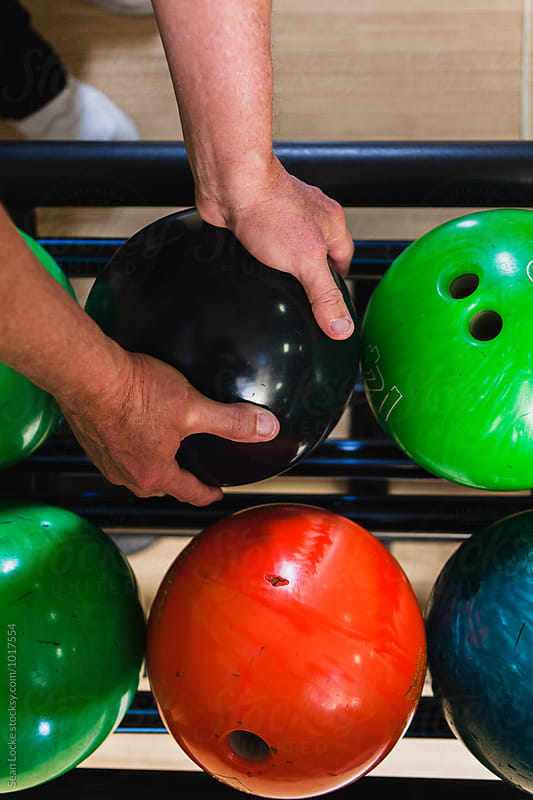 Bowling: Looking Down At Mature Hands Picking Up Ball by Sean Locke for Stocksy United