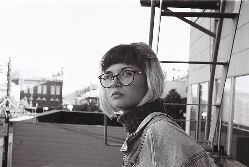 Portrait of young woman on fire escape  by Jesse Morrow for Stocksy United