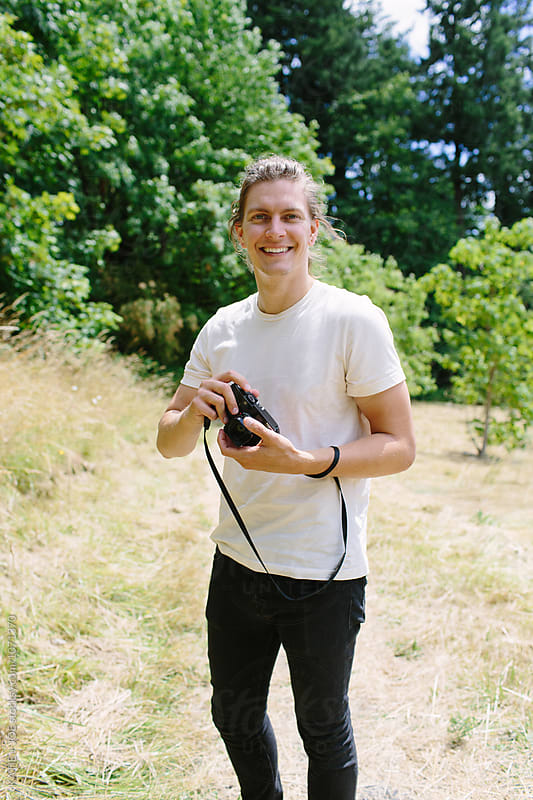 Man smiling and holding a camera outside by KATIE + JOE for Stocksy United