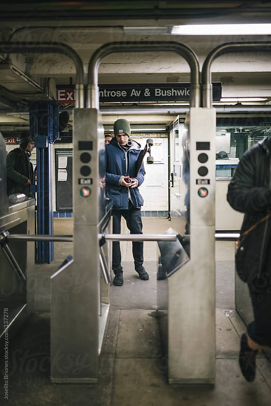 Young Male Student Going Through New York Subway Turnstile by Joselito Briones for Stocksy United
