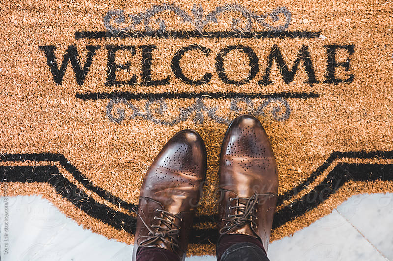 Welcome doormat and oxford shoes by Vera Lair for Stocksy United