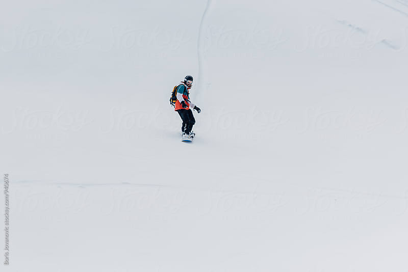 Man riding a snowboard down the slope by Boris Jovanovic for Stocksy United
