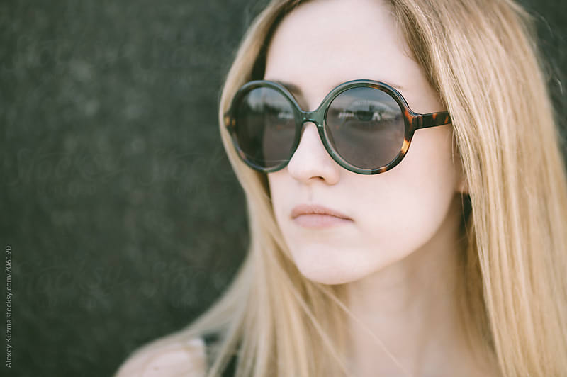 portrait of real young woman with round vintage sunglasses by Alexey Kuzma for Stocksy United