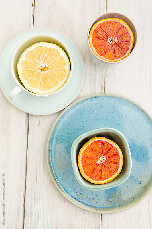 Blood orange and lemon halves in cups on plates by Elisabeth Coelfen for Stocksy United
