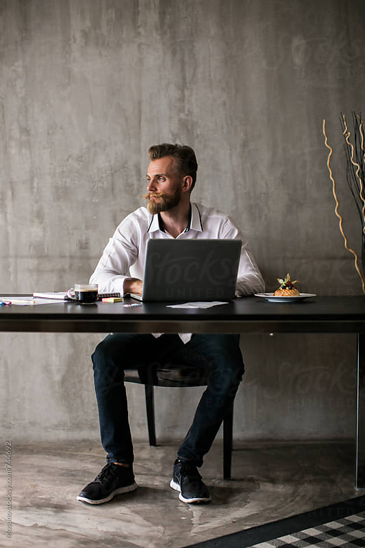 Man Sitting at the Desk and Looking Away by Mosuno for Stocksy United