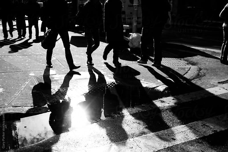 People crossing a wet zebra crossing in the city by Gary Parker for Stocksy United