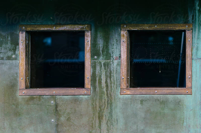 Two copper-trimmed square windows on a verdigris wall by James Jackson for Stocksy United