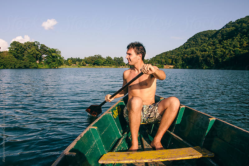 Man rowing on a boat on a lake by Alejandro Moreno de Carlos for Stocksy United
