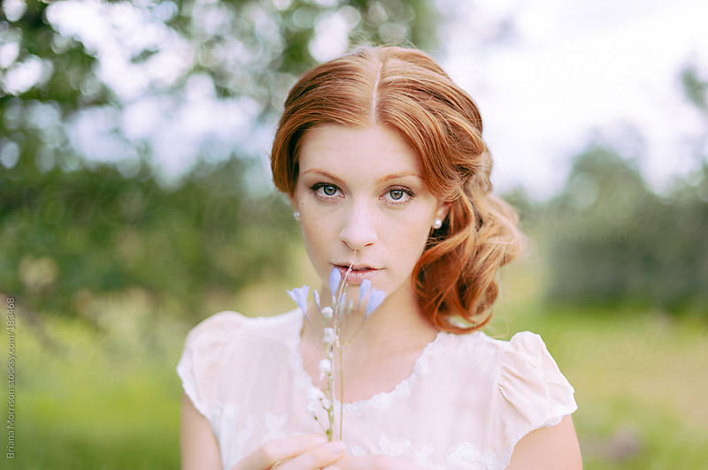 Portrait of a Woman with Red Hair in Vintage Silk Dress holding Flowers by Briana Morrison for Stocksy United