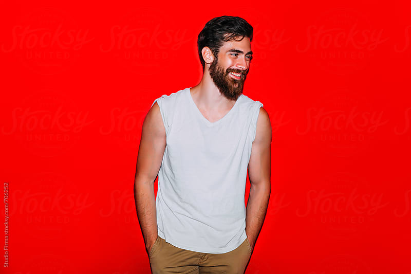 Young Man on Red Background. by Studio Firma for Stocksy United