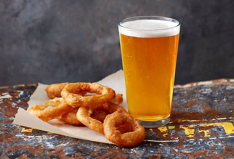 Light beer with onion rings on distressed metal surface by Sherry Heck for Stocksy United
