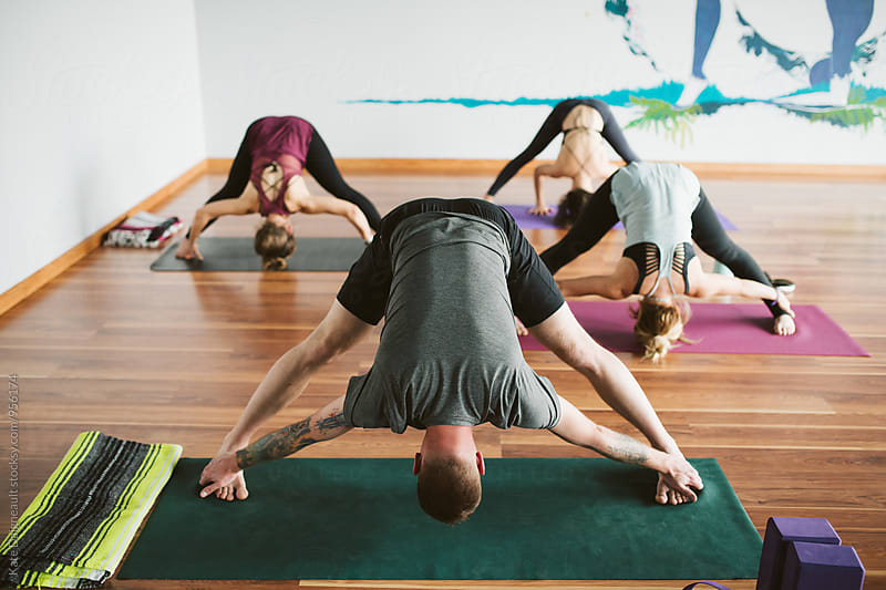 Group of young adults stretching in yoga class by Kate Daigneault for Stocksy United