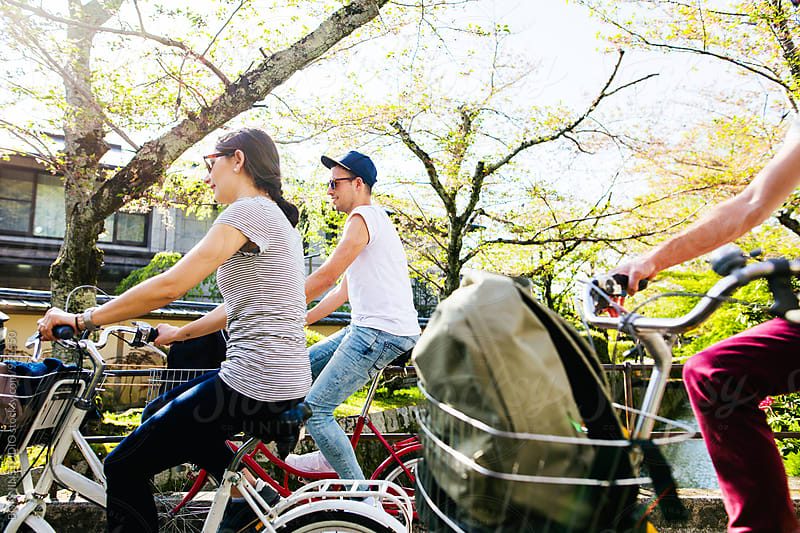 Side view of friends riding their bicycle in spring. by BONNINSTUDIO for Stocksy United