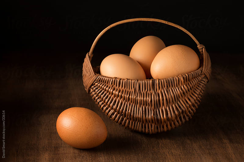Brown free-range eggs in a small hand woven basket by David Smart for Stocksy United