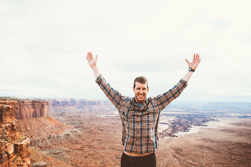 Man with Raised Hands at Desert Overlook by michelle edmonds for Stocksy United