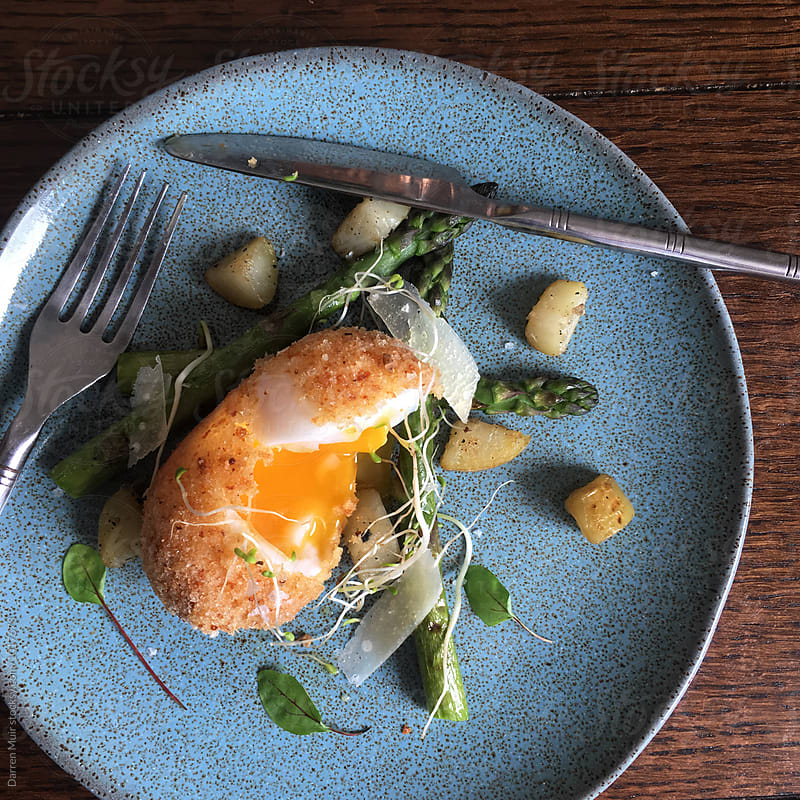 Brunch: Crispy duck egg with jersey royals and asparagus. by Darren Muir for Stocksy United