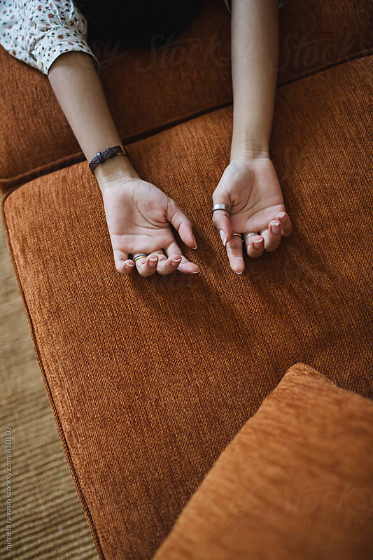 Female hands on the couch by michela ravasio for Stocksy United