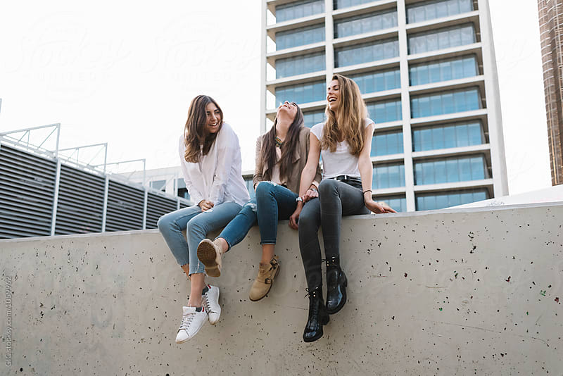 Three happy girl friends having fun in the city by Simone Becchetti for Stocksy United