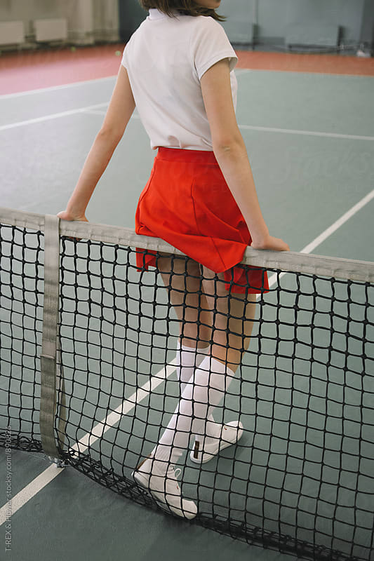 Young female tennis player in red skirt on net by Danil Nevsky for Stocksy United