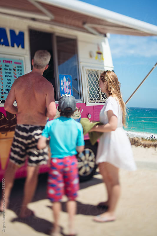 Family at an ice cream van at the beach in summer by Angela Lumsden for Stocksy United