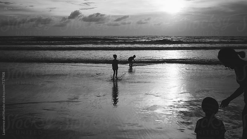 A family spends time with one another on the beach at sunset. by Lawrence del Mundo for Stocksy United
