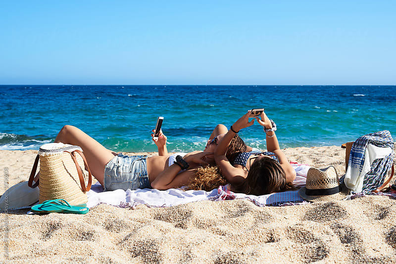 Girls on beach blanket using phones by Guille Faingold for Stocksy United