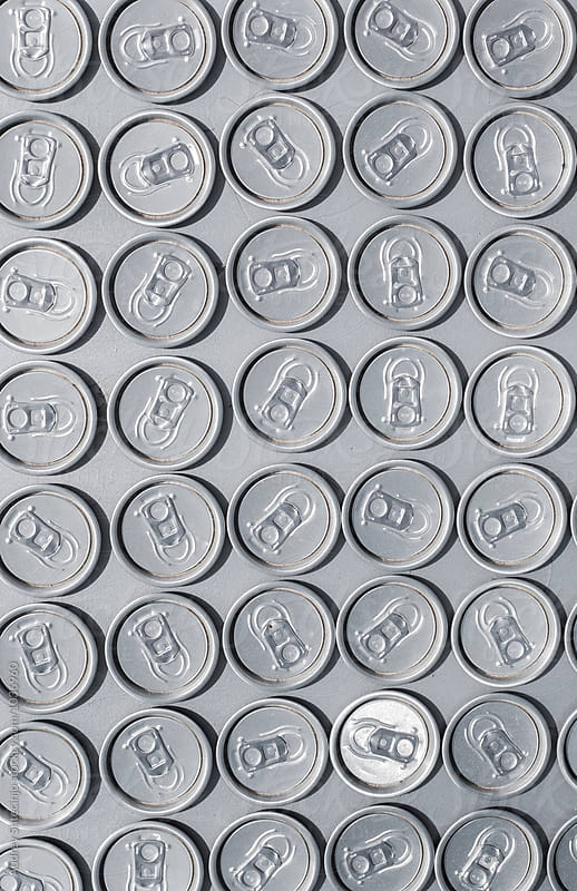 Repetition of plugs/tops of soda cans.  by Audrey Shtecinjo for Stocksy United