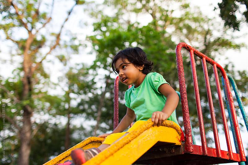 Little girl on a slide at a park by Saptak Ganguly for Stocksy United