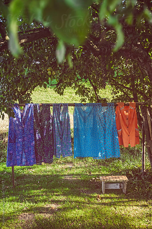 Colourful dresses drying in the garden. by Marija Savic for Stocksy United