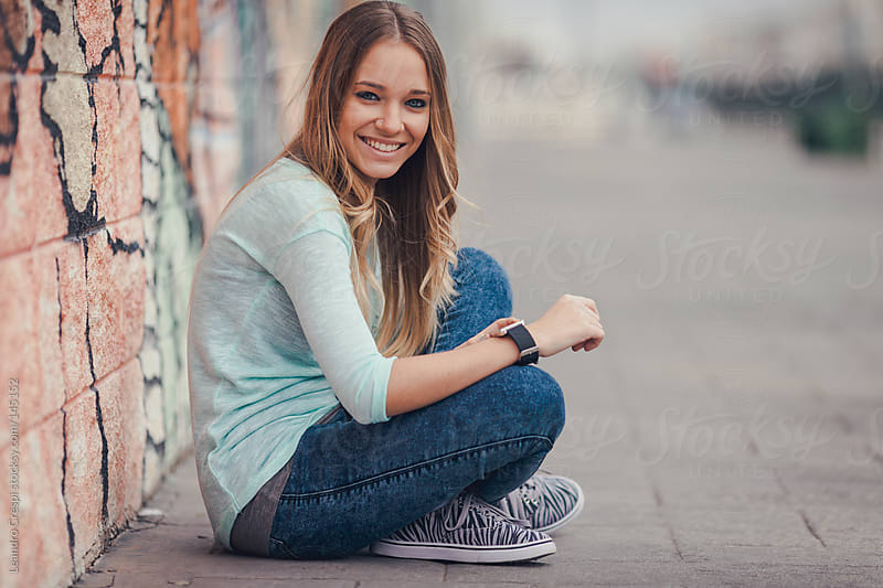 Happy woman using smartwatch by Leandro Crespi for Stocksy United
