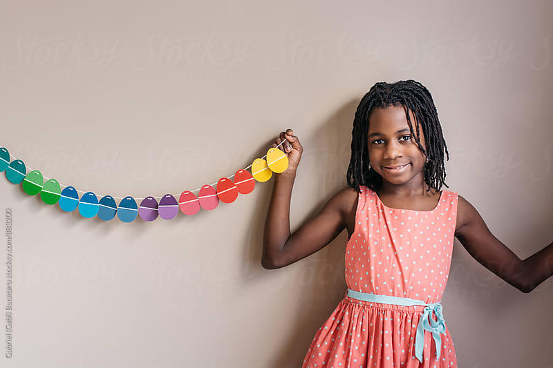 Smiling black girl and Easter egg garland by Gabriel (Gabi) Bucataru for Stocksy United
