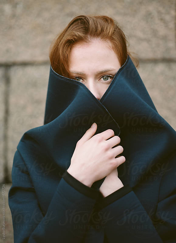 Woman wrap herself in navy neoprene coat by Lyuba Burakova for Stocksy United