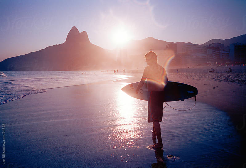 surfer going for a sunset surf in Rio de Janeiro, Brasil by Jan Bijl for Stocksy United