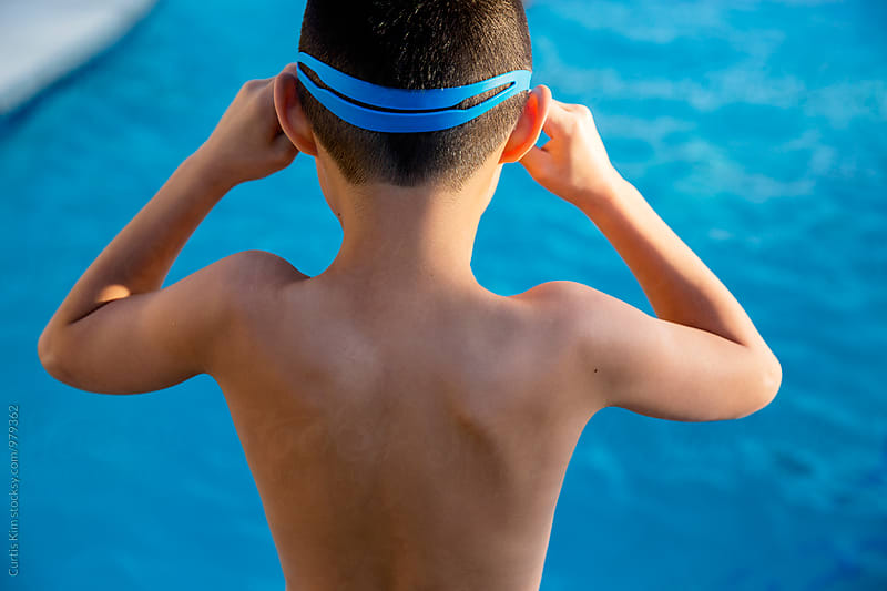 Little boy putting on his goggles before a swim by Curtis Kim for Stocksy United