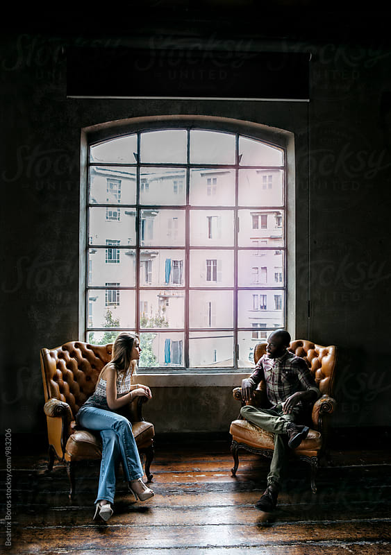 Multi-ethnic couple by the window in two armchairs talking to each other by Beatrix Boros for Stocksy United