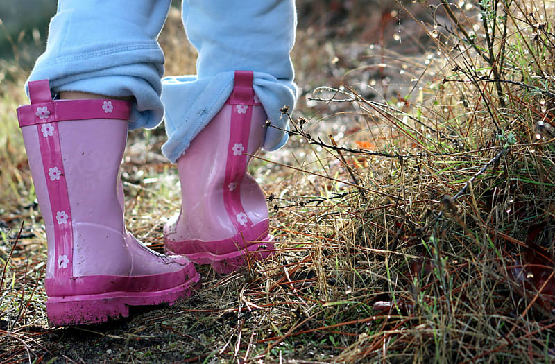 Little girl in pink rubber rain boots exploring after the rain by Carolyn Lagattuta for Stocksy United