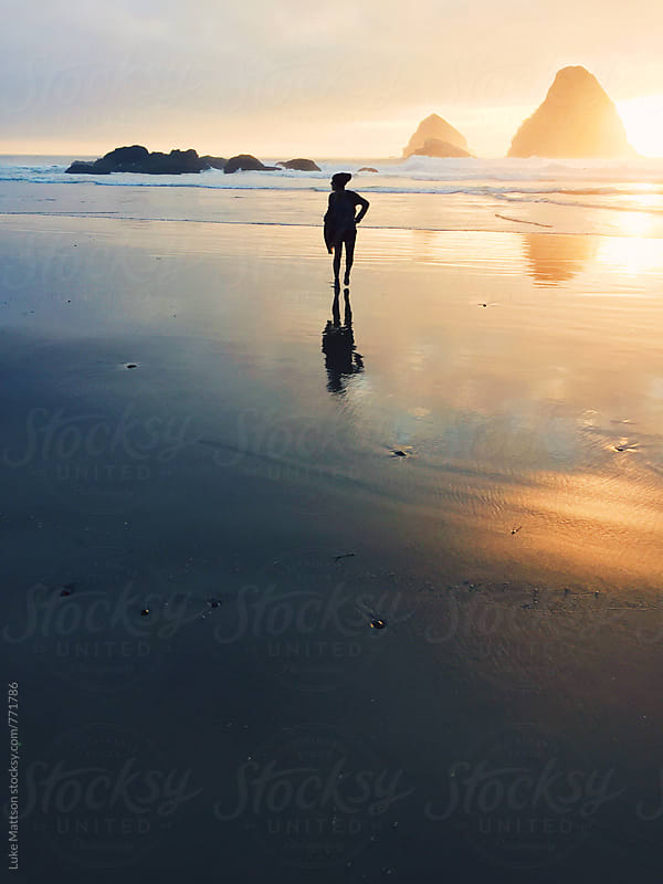 Young Woman Standing On Reflective Ocean Shore At Sunset by Luke Mattson for Stocksy United
