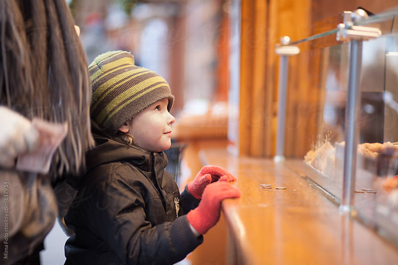 Boy looking at vendor shop at Christmas Market by Mima Foto for Stocksy United