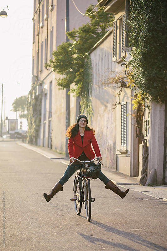 Young woman having fun with bicycle by michela ravasio for Stocksy United