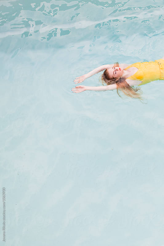 Young woman in the swimming pool by Jovana Rikalo for Stocksy United