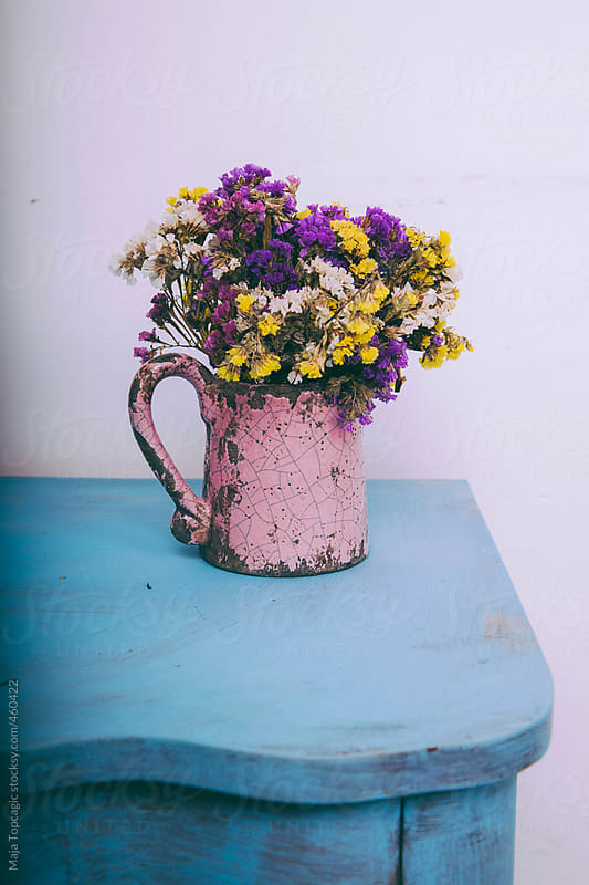A pink vase with colourful flowers on a blue table indoors by Maja Topcagic for Stocksy United