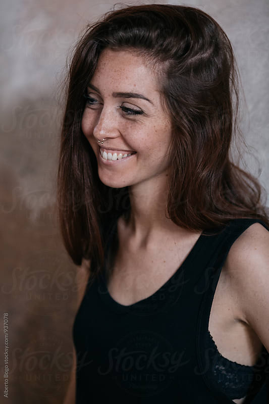 Smiling woman with freckles looking away by Alberto Bogo for Stocksy United